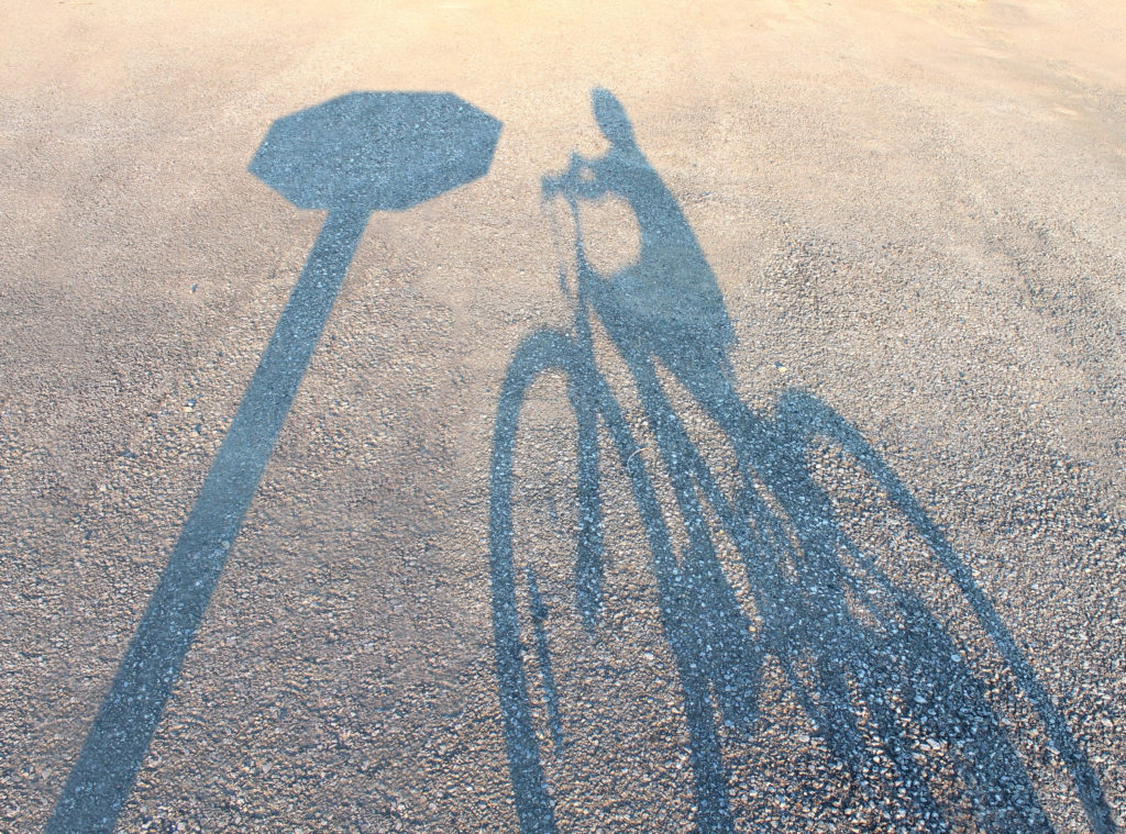 Shadow of bike and stop sign.